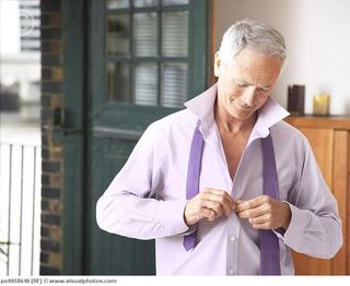 Man_in_bedroom_getting_dressed_for_work_pe0058640
